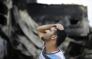 Seorang warga Palestina melihat pada pabrik makanan milik keluarganya, yang menurut saksi mata ditembaki oleh tentara Israel selama terjadinya penyerangan Israel ke Jalur Gaza, di Deri al Balah di pusat Jalur Gaza