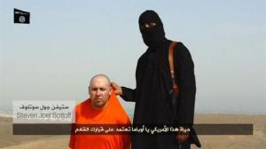 Seorang milisi IS berbicara di samping seorang lelaki yang diakui sebagai seorang jurnalis Amerika bernama di sebuah lokasi yang tak diketahui-REUTERS/Social Media Website via REUTERS TV
